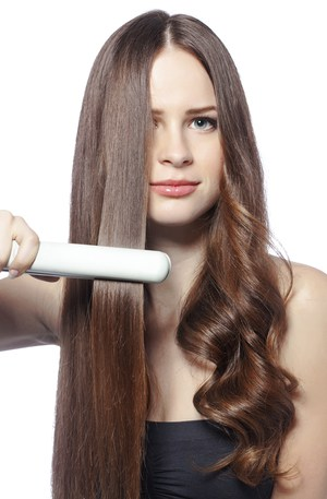 Beautiful girl using hair styler for straight hair and curls