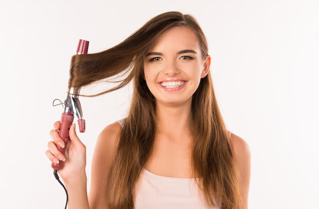 girl curling fine hair with curling iron