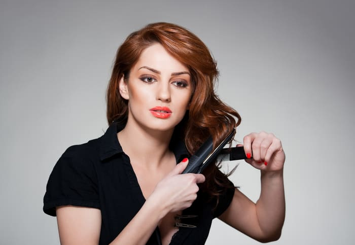 woman using the best flat iron for curling hair